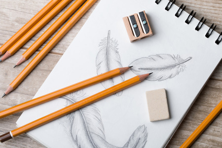 pensil: Close-up view of artists or designers table. Pencils, sharpner and eraser laying on sketch book with hand-drawn feathers