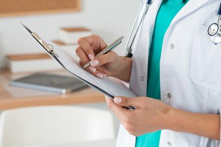 Здоровье: Крупным планом вид женщина-врач руки заполняя регистрационную форму пациента. Здравоохранение и медицинская концепция