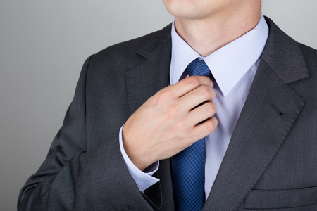 exacting: Well dressed business man adjusting his neck tie