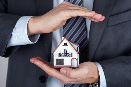 purchases: Business man holding house model. Protecting gesture. Property insurance and security concept. Stock Photo