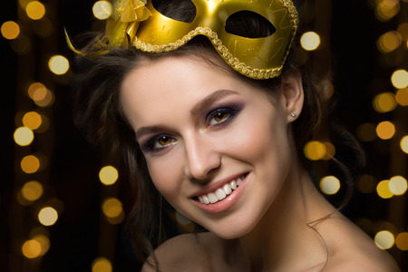 event party festive: Portrait of beautiful young smiling woman wearing golden party mask with golden lights on background