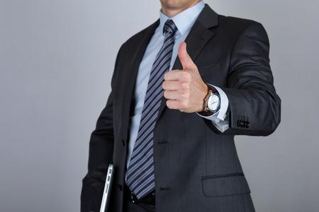 비즈니스 남자 노트북을 들고와 최대 회색 배경 위에 엄지 손가락을 보여주는. 비즈니스 성공의 개념
