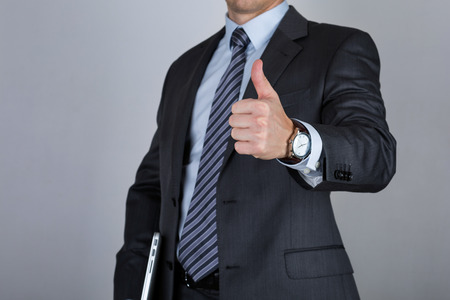 great suit: Business man holding laptop and showing thumbs up over gray background. Business success concept