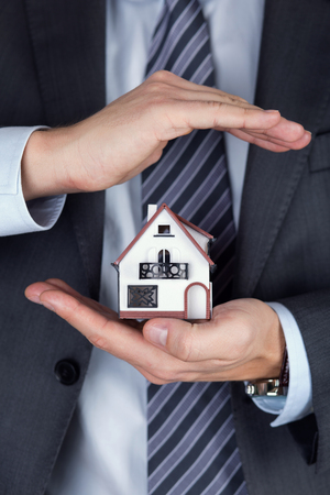 business security: Business man holding house model. Protecting gesture. Property insurance and security concept. Stock Photo