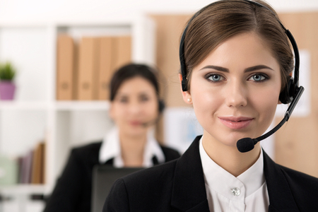 operator: Portrait of call center worker accompanied by her team. Smiling customer support operator at work. Help and support concept
