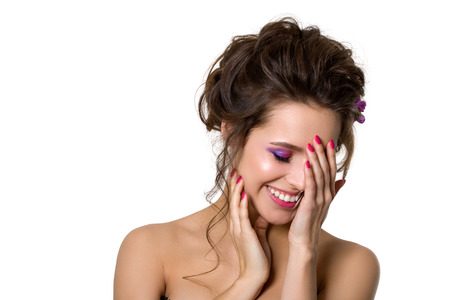 smiling face: Portrait of young beautiful smiling woman touching her face over white background. Bridal coiffure and pink wedding make-up. Pink lips, smokey eyes and manicure. Copy space Stock Photo