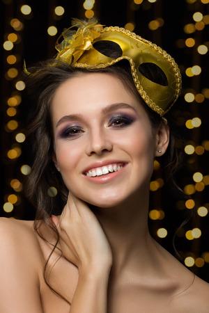 mujer bonita: Retrato de la mujer sonriente joven hermosa que lleva la m�scara de oro del partido con luces doradas sobre fondo