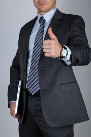 hand job: Business man holding laptop and showing thumbs up over gray background. Business success concept