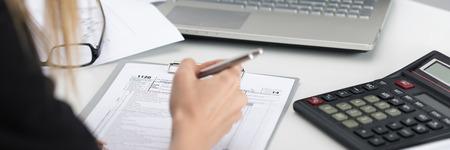 税務フォームを記入女性の手のショットを閉じる。貯蓄、財政および経済のコンセプトです。レター ボックス形式 写真素材