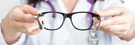 女性の oculist 医師の手が黒い眼鏡のペアを与えること。良いビジョン コンセプト。レター ボックス形式