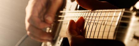 guitarra: Las manos del hombre tocando la guitarra eléctrica. técnica de plegado. Foto oscura. formato de buzón