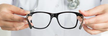 oculist: manos Mujer del médico oculista que dan un par de gafas negras. Buen concepto de la visión. formato de buzón