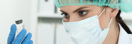 scientific research: Medical doctor in protective gloves and surgical mask and hat looking at small flask with liquid in laboratory. Scientific research, healthcare and medical concept. Letter box format