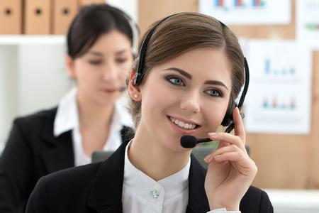 professional woman: Portrait of call center worker accompanied by her team. Smiling customer support operator at work. Help and support concept