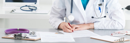 Female medical doctor writing something sitting at her office. Healthcare and medical concept.. Letter box format Banque d'images