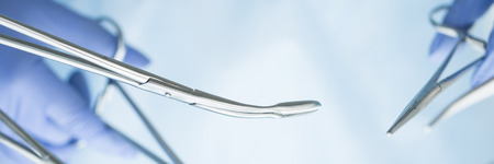 letter box: Close-up of doctors hands holding surgical clamps. Medical background. Letter box format