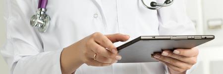 Vrouwelijke Arts Holding Tablet PC. Doctor's hands close-up. Medische dienst en gezondheidszorg concept. letterboxformaat Stockfoto