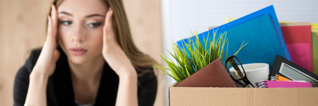 employment issues: Young dismissed female worker sitting near the carton box with her belongings in office not knowing what to do next. Getting fired concept.