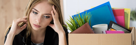 employees: Young dismissed female worker sitting near the carton box with her belongings in office not knowing what to do next. Getting fired concept. Letter box format