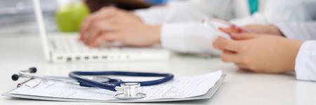 医学博士作業テーブル。聴診器に焦点を当てます。バック グラウンドで動作している 2 つの女性医学医師。健康・医療薬や処方が空白でクリップ ボ 写真素材
