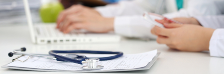 Medicine doctor's working table. Focus on stethoscope. Two female medicine doctors operating on background. Healthcare and medical conceptBottle of pills and stethoscope laying on clipping board with prescription blank. Medicine doctor's working table. He