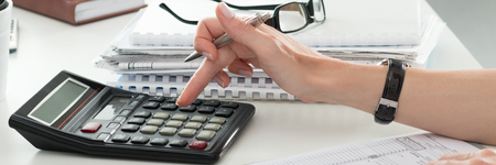 working desk: Close up of female accountant or banker making calculations. Savings, finances and economy concept