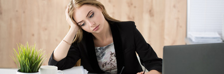 work stress: Tired business woman sitting at her working place. Overwork, working overtime and stress at work concept. Letter box format