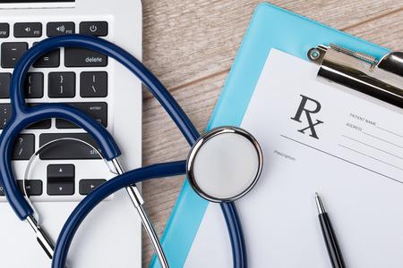 recetas medicas: Primer plano vista superior de lugar de trabajo médico. Estetoscopio, computadora portátil y forma de prescripción en blanco en la superficie de madera.