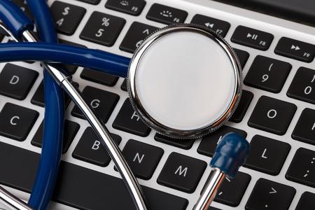 computer tech: Stethoscope head lying on computer keyboard closeup. Medical concept. Modern medicine and high tech equipment concept