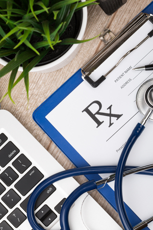 phonendoscope: Close-up top view of pharmaceutical chemist working place. Stethoscope, laptop and blank prescription form on wooden surface. Healthcare, medical and pharmaceutical concept.