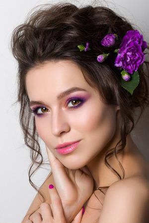 bridal salon: Portrait of young beautiful woman with violet flowers in her hair posing over white background. Bright summer fashion make up. Pink lips and smokey eyes.