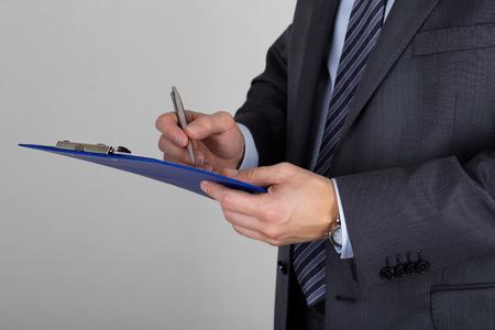 ビジネスの男性クリップボードを保持し、ドキュメントに署名します。購読契約またはパートナーシップ契約
