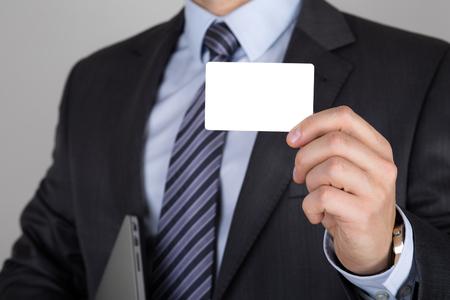 El hombre de negocios que sostiene la tarjeta de visita blanca. reunión de negocios o un concepto de presentación