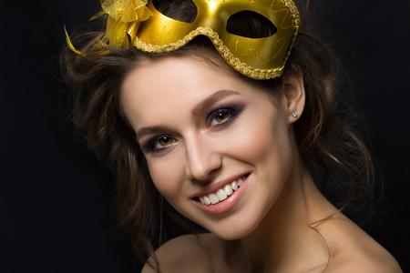 make over: Portrait of young beautiful woman wearing golden party mask. Smokey eyes makeup. Studio shot. Stock Photo