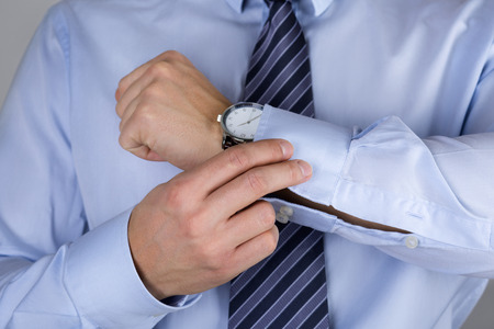 Man fastens his cuff links close-up. Businessman or fiance preparing himself for going out. Reklamní fotografie - 53127209