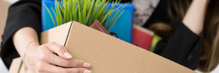 unemployed dismissed: Young dismissed female worker in office holding carton box with her belongings. Getting fired concept. Letter box format Stock Photo