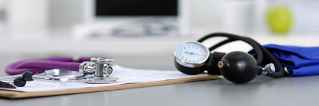 physicians office: Medicine doctors working place. Stethoscope and manometer lying on table at physicians office. Healthcare and medical concept. Letter box format