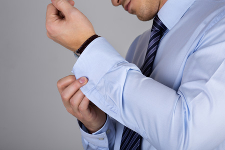 formal dressing: Man fastens his cuff links close-up. Businessman or fiance preparing himself for going out.
