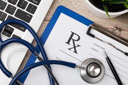 recetas medicas: Primer plano vista superior de lugar de trabajo químico farmacéutico. Estetoscopio, computadora portátil y forma de prescripción en blanco en la superficie de madera. Cuidado de la salud, concepto médico y farmacéutico.