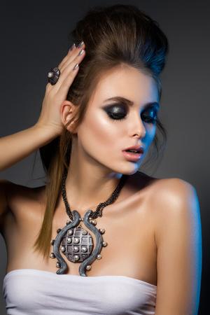 make over: Beauty portrait of young glamorous woman touching her hair. Smokey eyes makeup. Studio shot.