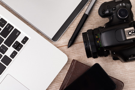 Close-up top view of photographer of graphic designer workplace. Laptop, graphic tablet, phone and photo camera on wooden table.