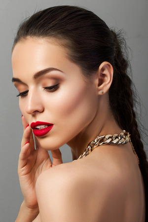 make over: Beauty portrait of young aristocratic woman with red lips and nails touching her face. Classic evening make up. Brown smokey eyes
