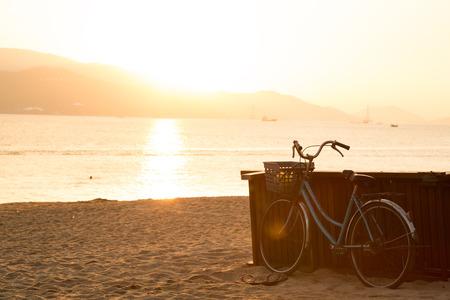 vacaciones en la playa: bicicleta azul que se coloca en la playa de arena durante el amanecer. La libertad y el concepto de la felicidad. Viejos colores de la sepia de moda. Publicación de vista de la tarjeta.