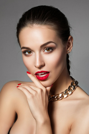 make up fashion: Beauty portrait of young aristocratic woman with red lips and nails touching her face. Classic evening make up. Brown smokey eyes