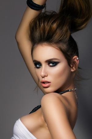beauty model: Portrait of young fashion model holding her pony tail. Smokey eyes make up. Studio shot. Stock Photo