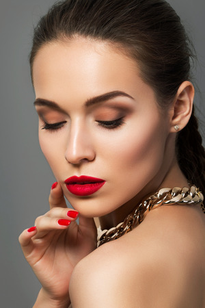 Beauty portrait of young aristocratic woman with red lips and nails. Classic evening make up. Brown smokey eyes