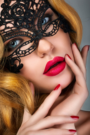 lace up: Portrait of young sensual woman wearing black lace party mask. Classic evening makeup with red lips and nails