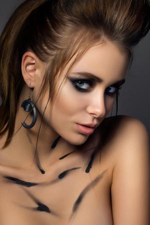 naughty woman: Beauty portrait of young glamorous woman with fashion make-up. Smokey eyes fashion make up. Studio shot. Stock Photo