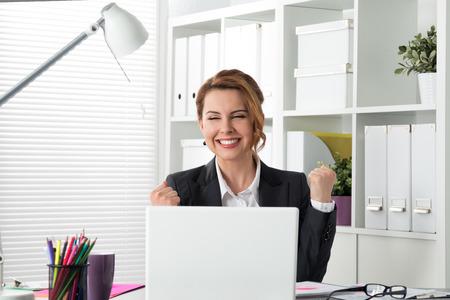 축하: 행복 젊은 성공적인 사업가의 초상화 팔을 위로 무언가를 축하합니다. 행복 한 여자는 사무실에 앉아서 노트북을 봐주세요. 긍정적 인 감정. 큰 거래,  스톡 콘텐츠