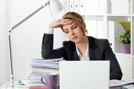 overworking: Portrait of tired businesswoman sitting at her office near huge heap of papers and holding her head. Woman dont know what to do. Problems, stress at work, overworking, deadline or redundancy concept